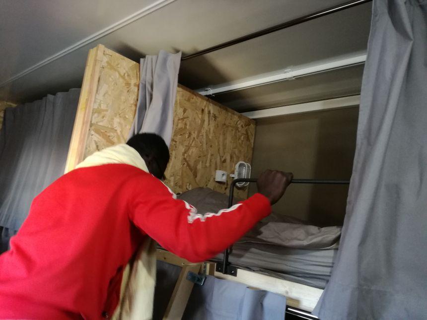 Ahmed, un habitant de la remorque, monte dans sa couchette
