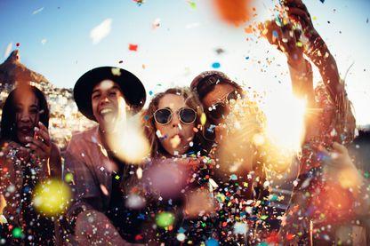 Groupe d'amis, des adolescent qui font la fête en soufflant et en jetant des confettis colorés sous la lumière du soleil du coucher du soleil.