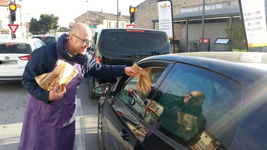 Un producteur offre un sachet de pommes et poires à un automobiliste de Coustellet