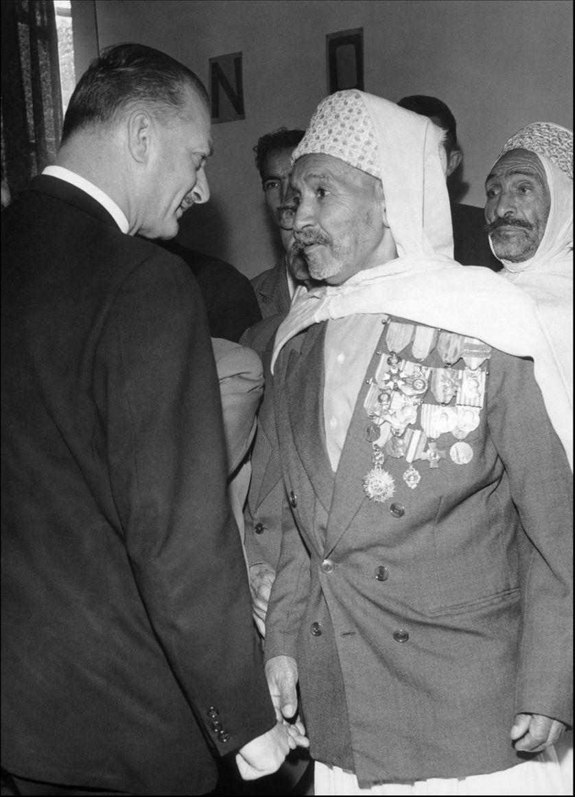 Photo datée de 1958, à Médéa, pendant la guerre d'Algérie, du délégué général du gouvernement pour l'Algérie, Paul Delouvrier, discutant avec un ancien combattant algérien lors de la tournée qu'il fit dans tout le pays