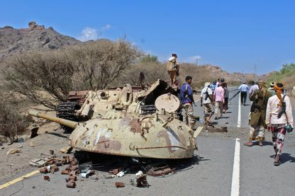 Les combattants yéménites fidèles au gouvernement soutenus par la coalition saoudienne se rassemblent autour de la tourelle et du corps d'un char détruit, près de la ville d'Al-Shurayja dans la province de Lahij