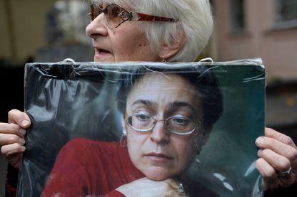 Femme tenant un portrait d'Anna Politkovskaïa