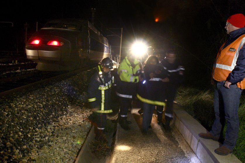 Des pompiers évacuent une voie après un accident voyageur.