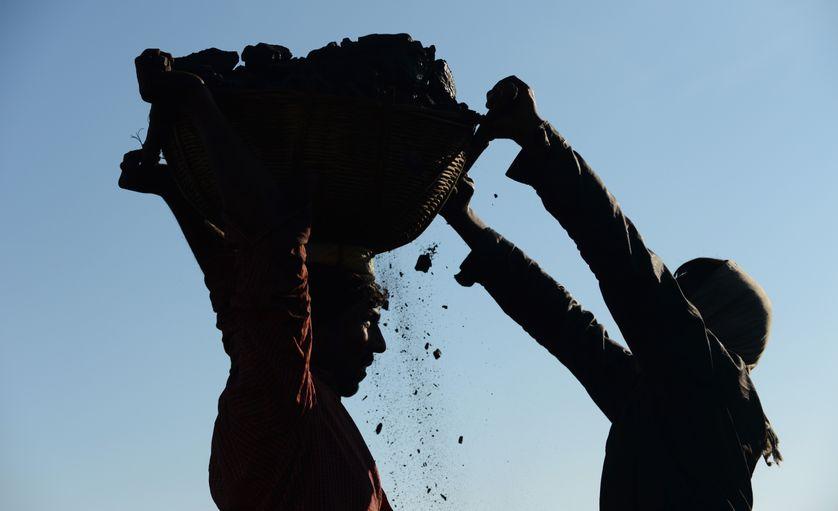 Des mineurs portant un panier rempli de charbon, près de Rymbai, au nord-est de l'Etat de Meghalaya, en Inde (janvier 2013)
