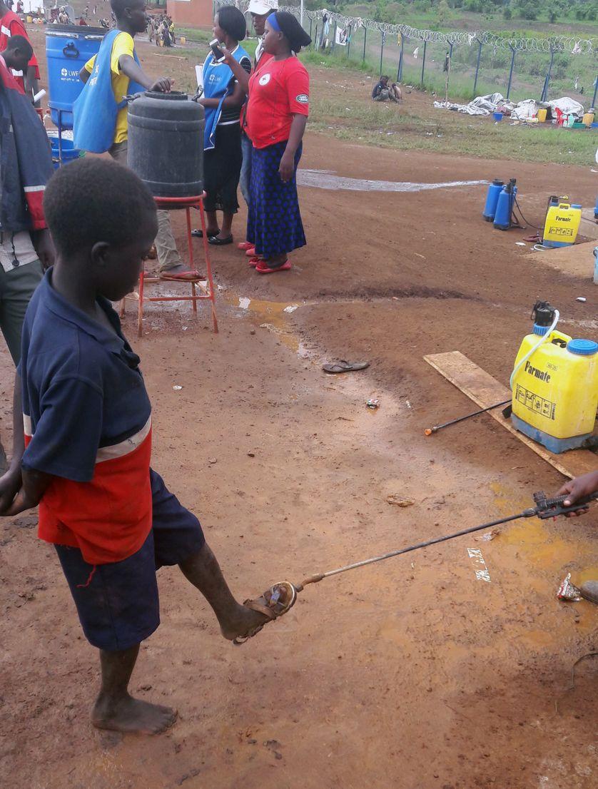 Les réfugiés transférés dans le centre de réception, des mesures sanitaires sont prises. Ici, la pulvérisation d'un désinfectant sous les chaussures. Une épidémie de choléra a récemment eu lieu.