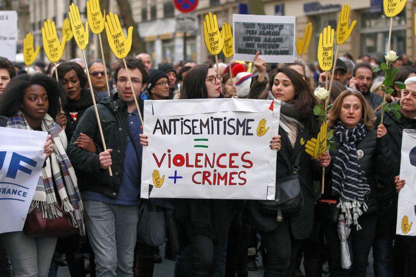 Des manifestants tiennent une pancarte contre l'anti-sémitisme lors de la marche blanche organisée à la mémoire de Mireille Knoll, le 28 mars 2018 à Paris