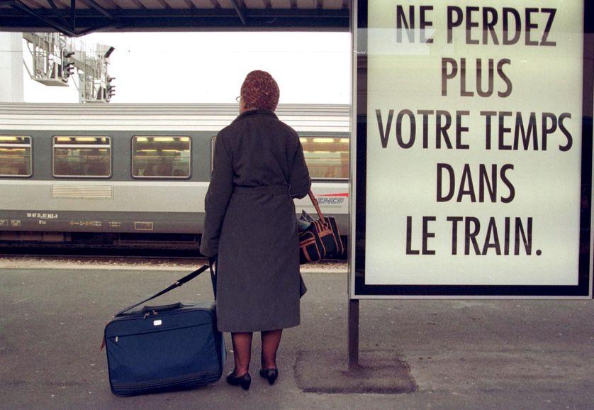 Une femme attend, sur un quai de la gare de Caen, un train pour Paris, 3 décembre 1998