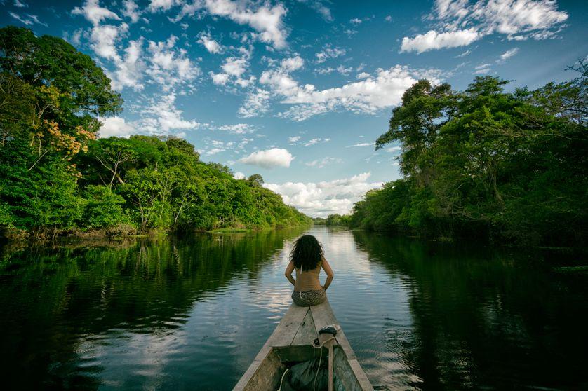 Une jeune femme navigue sur une rivière amazonienne au Pérou.