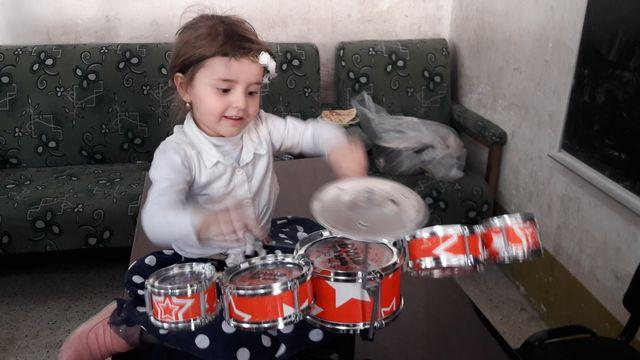 Une fillette apprend à jouer de la batterie