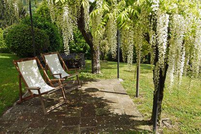 Une paire de chaises longues vides sous un baldaquin ombragé dans un jardin luxuriant au printemps, en Italie.