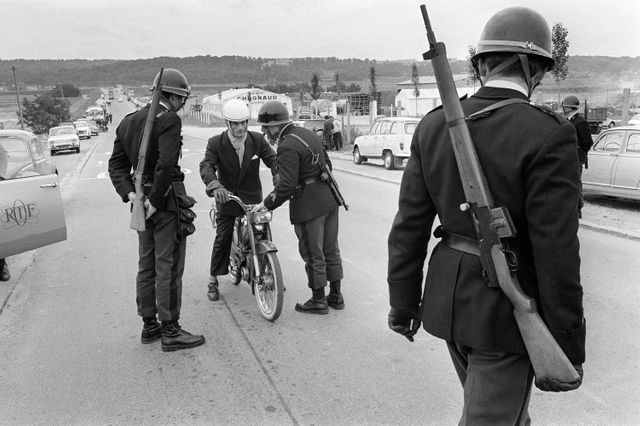 Les forces de police anti-émeutes contrôlent un homme circulant à moto en  juin 1968 devant l'usine Renault de Flins.