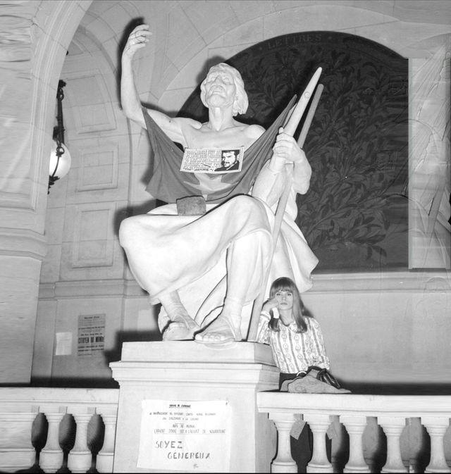 Une jeune étudiante se repose dans le hall d'entrée de la Sorbonne, le 21 mai 1968 à Paris, au pied d'une statue sur laquelle le drapeau chinois, une photo et une citation du révolutionnaire cubain Che Guevara ont été accrochés, lors d'une réunion d'
