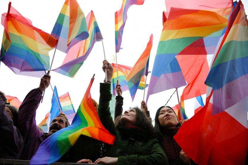 Les participants agitent leurs drapeaux arc-en-ciel, drapeau de la communauté lesbienne, gay, bisexuelle et transsexuelle (LGBT).