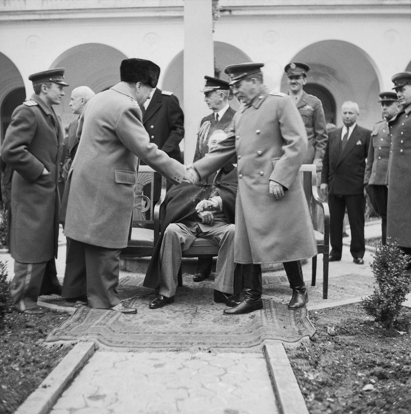 La Conférence de Yalta en février 1945, Winston Churchill serre la main de Staline. Le président Roosevelt est assis derrière.