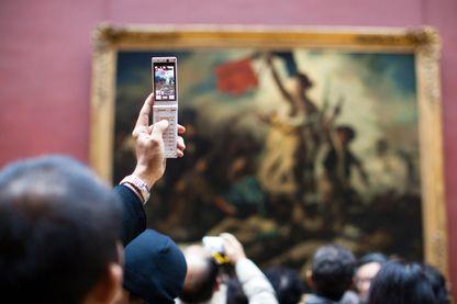 """Foule de visiteurs rassemblés devant """"La liberté guidant le peuple"""". Eugène Delacroix a peint ce tableau en 1830, alors qu'éclatait à Paris la révolution des Trois Glorieuses"""