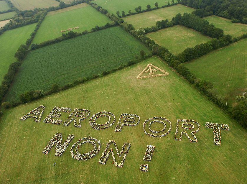 """Des personnes opposées à l'implantation d'un nouvel aéroport, ont réalisé une chaîne humaine pour écrire """"Aéroport Non !"""", le 25 juin 2006 dans un champs de Notre-Dame-des-Landes près de Nantes."""