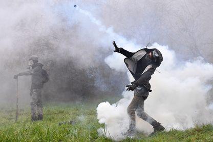 Un manifestant lance une bombe lacrymogène contre les forces anti-émeutes alors que des affrontements éclatent lors d'une opération de police visant à raser le camp de ZAD (Zone à Defendre) à Notre-Dame-des-Landes.