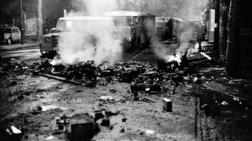 Des cars de CRS au milieu des débris fumant, dans une rue dépavée du Quartier latin, le 23 mai 1968.