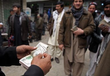 In this Jan. 12, 2015 file photo, an Afghan money changer, left, counts a pile of currency at the Money and Exchange Market in Kabul.