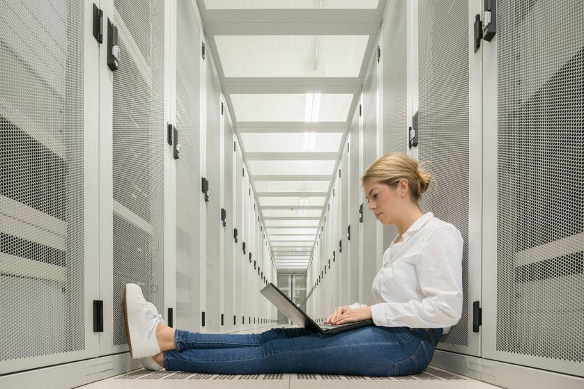 Une femme assise au milieu de serveurs informatiques