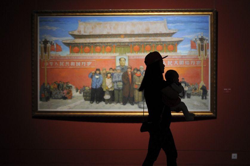 Une femme porte un bébé au China National Art Museum à Pékin