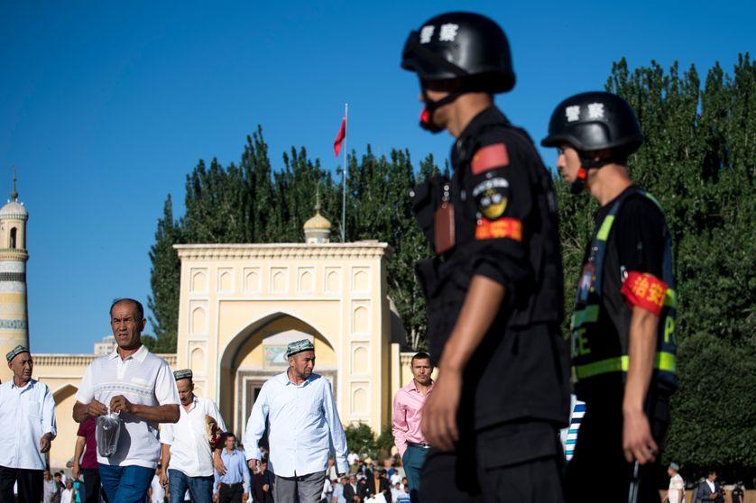 Des officiers de police patrouillent devant une mosquée au Xinjiang (Chine), le 26 juin 2017