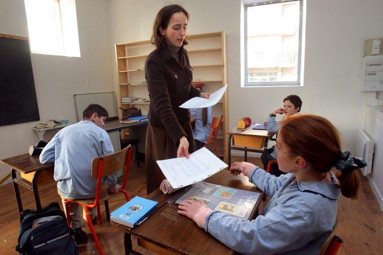 Un professeur rend les copies à des élèves de sixième.