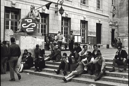 Mai 68 au pied de la Sorbonne, des étudiants attendent. A gauche, le logo du PSU.