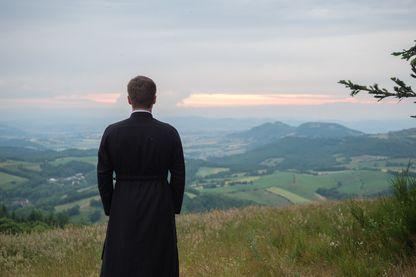 Un Prêtre seul méditant en haut d'une colline devant la nature.