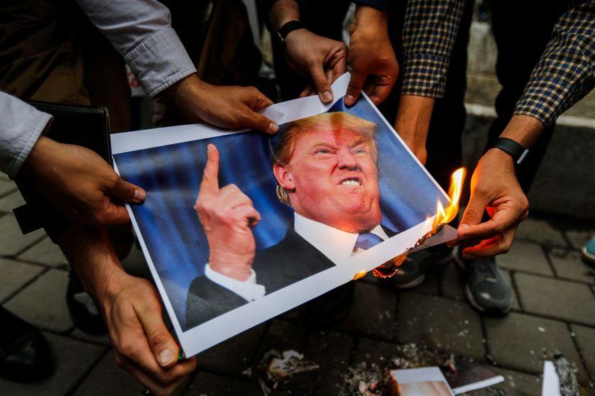 Des Iraniens brûlent une photographie de Donald Trump à Téhéran le 9 mai 2018