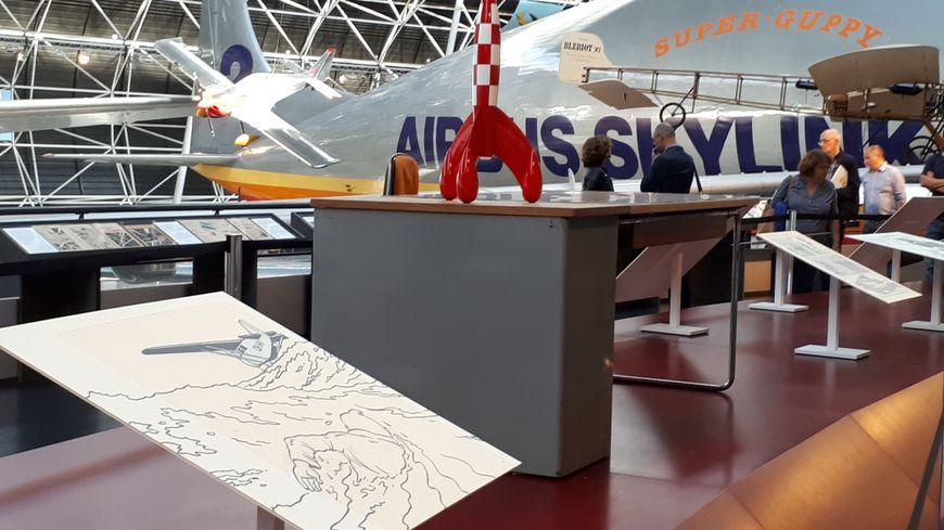"""La fusée inventée par Hergé dans """"Objectif Lune"""" trône sur le bureau de l'auteur au milieu des avions du musée."""