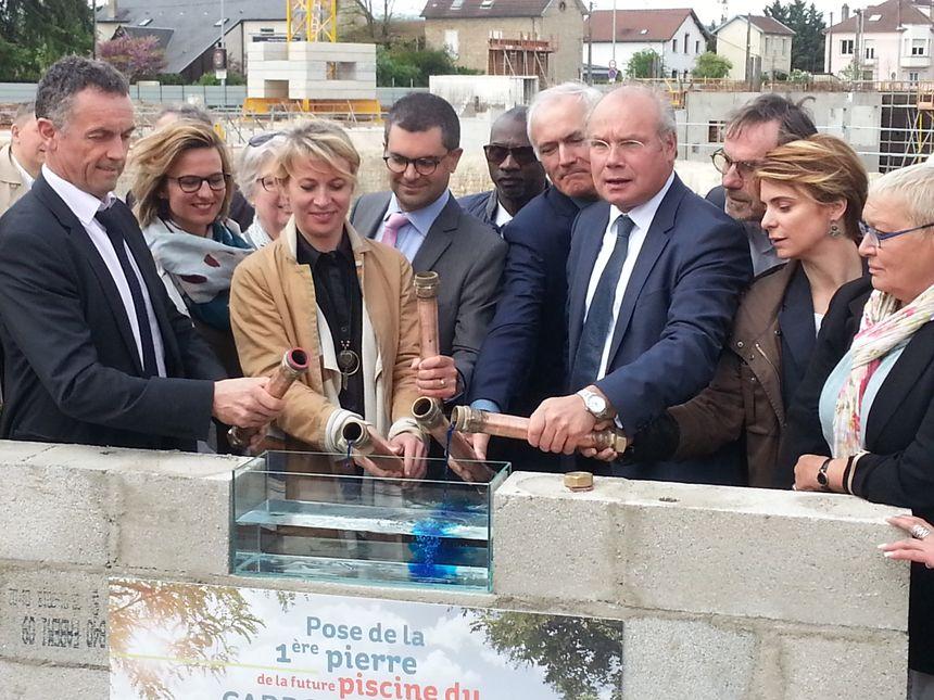 """Nathalie Koenders, première adjointe à la ville de Dijon et Pierre Pribétich, premier vice-président à Dijon métropole posent le """"premier liquide"""" de la future piscine du Carrousel"""