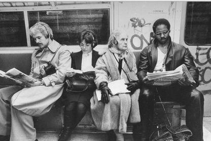 Quatre personnes dans le métro à New-York, dans les années 80, écoutent leurs walkmans.