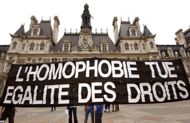 Des militants contre l'homophobie déploient une banderole, le 5 juin 2004 devant l'hôtel de ville de Paris, pour soutenir la démarche de Noël Mamère qui célèbre simultanément le mariage de deux homosexuels à Bègles.