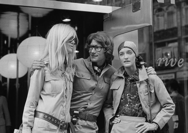 """Yves Saint Laurent avec les mannequins Betty Catroux (à gauche) et Loulou de la Falaise, devant sa boutique """"Rive Gauche"""" en 1969 à Paris"""
