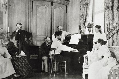 Le compositeur Claude Debussy au piano, entouré de sa famille et de celle de son confrère et ami Ernest Chausson en 1893.