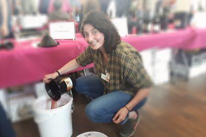 Maelle, bénévole, récupère le reste des  vins dégustés