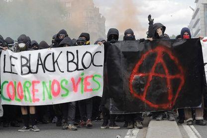 Black Bloc  brandissent des bombes fumigènes et une banderole portant la mention «Le bloc noir colore nos vies» et représentant le symbole anarchiste alors qu'ils participent à une marche pour le rassemblement annuel des travailleurs du 1er mai à Par