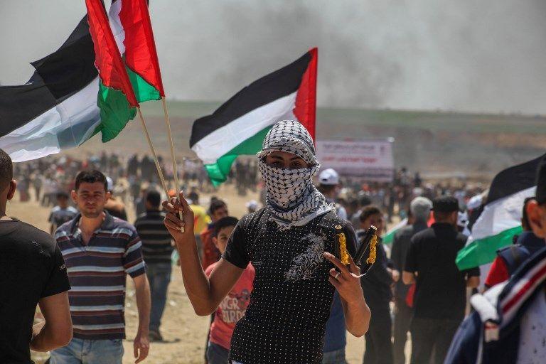 Le drapeau palestinien flotte dans les airs à la frontière entre Israël et la bande de Gaza le 14 mai 2018