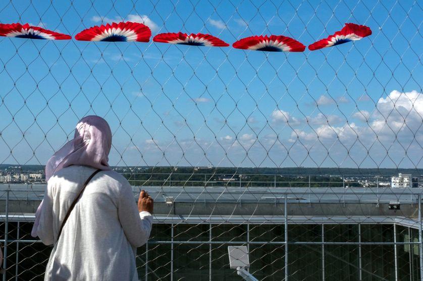 Une femme regarde le défilé aérien du 14 juillet à Paris