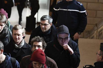 Julien Coupat arrive à son procès avec à ses côtés une personne portant un masque représentant le procureur général Olivier Christen, et celle du groupe des sept autres membres, le 13 mars, 2018 au palais de justice de Paris.