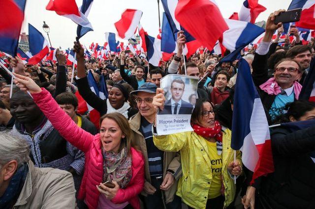 Supporters d'Emmanuel Macron réunis devant la Pyramide du Louvre à Paris le 7 mai 2017, dans l'attente des résultats des scrutins du second tour de l'élection présidentielle...