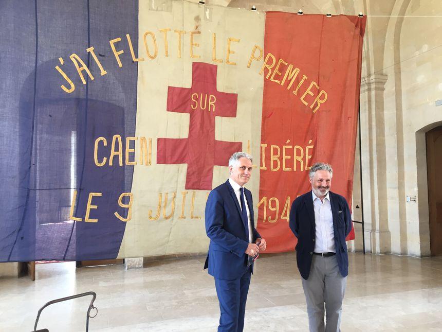 Joël Bruneau, maire de Caen, et Stéphane Grimaldi, directeur du Mémorial, devant le drapeau français qui a flotté sur Caen libéré.