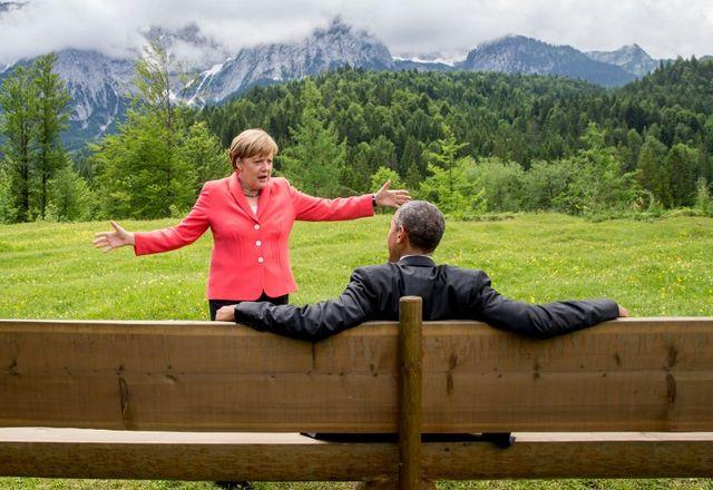 Angela Merkel (L) fait un geste en discutant avec le président américain Barack Obama assis sur un banc devant le château d'Elmau après une séance de travail du sommet du G7 près de Garmisch-Partenkirchen, dans le sud de l'Allemagne, le 8 juin 2015.