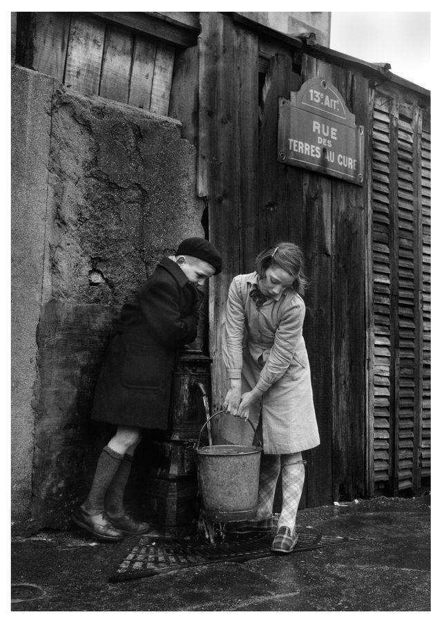 Enfants prenant de l'eau à la fontaine, rue des Terres-au-Curé Paris, 1954
