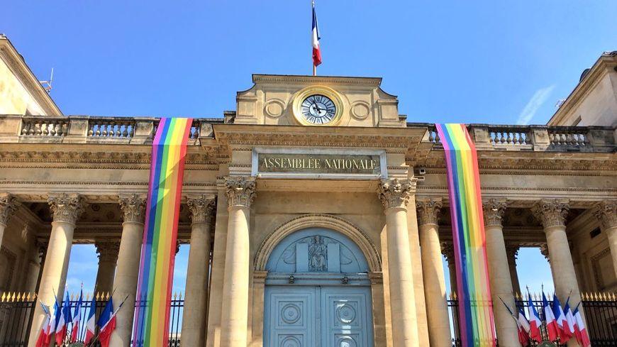 Deux drapeaux aux couleurs LGBT ornent la façade de l'Assemblée nationale ce samedi.