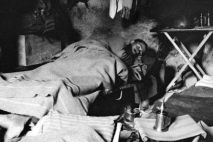 Poilu au repos, couche dans sa cagna (abri de fortune aménage dans les tranchées du front