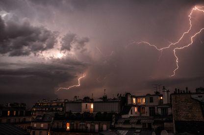 Orage avec des éclairs dans la nuit au dessus d'une ville.