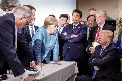 Le président Donald Trump (R) discute avec la chancelière allemande Angela Merkel (C) et entouré d'autres dirigeants du G7 lors d'une réunion du sommet du G7 à La Malbaie, Québec, Canada.