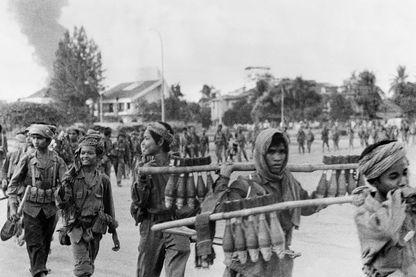 De jeunes khmers rouges portent des obus de mortier le 17 avril 1975 pendant qu'ils entrent à Phnom Penh